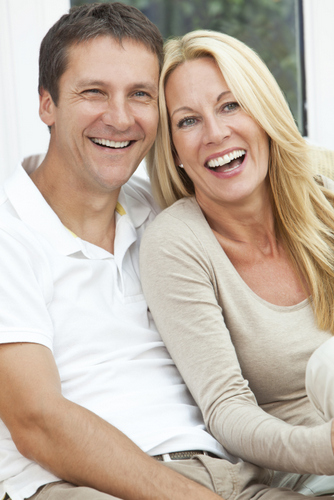 Middle Age Couple Smiling and Sitting after getting dental implants by their Ann Arbor dentist.