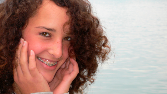 girl with curly hair and braces from her Ann Arbor dentist at Everwell Dentistry.
